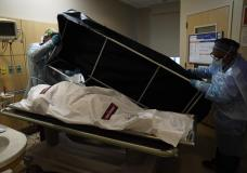 FILE - In this Jan. 9, 2021 file photo, transporters Miguel Lopez, right, Noe Meza prepare to move a body of a COVID-19 victim to a morgue at Providence Holy Cross Medical Center in the Mission Hills section of Los Angeles. The U.S. death toll from COVID-19 has topped 600,000, even as the vaccination drive has drastically slashed daily cases and deaths and allowed the country to emerge from the gloom. (AP Photo/Jae C. Hong, File)