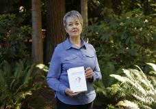 Karen McKnight stands in her backyard on Saturday, June 19, 2021, in Sammamish, Wash., holding two books written by her brother Ross Bagne of Cheyenne, Wyo. Nearly all COVID-19 deaths in the United States now are in people who weren't vaccinated like Bagne, a staggering demonstration of how effective the vaccines have been (AP Photo/John Froschauer)