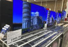 A sign displays the price of a 65-inch television lined up with countless other televisions in a Costco warehouse on Thursday, June 17, 2021, in Loen Tree, Colo. The Commerce Department said Thursday, June 24 that growth in the gross domestic product, the country's total output of goods and services, was unchanged from two previous estimates.(AP Photo/David Zalubowski)