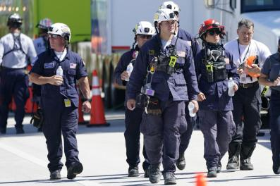 Members of the South Florida Urban Search and Rescue team walk near the Champlain Towers South condo building, where scores of victims remain missing more than a week after it partially collapsed, Saturday, July 3, 2021, in Surfside, Fla. (AP Photo/Lynne Sladky)