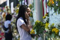 Evalyn Fregene holds a bouquet of flowers as she pays her respects at a makeshift memorial near the Champlain Towers South condo building, where scores of victims remain missing more than a week after it partially collapsed, Saturday, July 3, 2021, in Surfside, Fla. (AP Photo/Lynne Sladky)