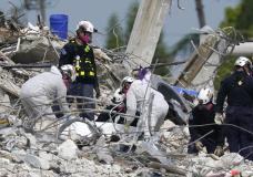 Rescue workers handle a tarp containing recovered remains at the site of the collapsed Champlain Towers South condo building, Monday, July 5, 2021, in Surfside, Fla. The remaining structure was demolished Sunday, which partially collapsed June 24. Many people remain unaccounted for. (AP Photo/Lynne Sladky)