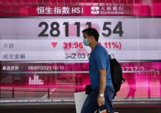 A man wearing a face a mask walks past a bank's electronic board showing the Hong Kong share index in Hong Kong, Tuesday, July 6, 2021. Asian shares were mixed in muted trading on Tuesday as oil prices surged higher after a meeting of oil producing nations was postponed. (AP Photo/Kin Cheung)