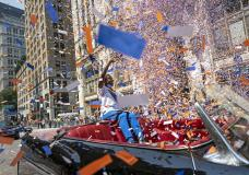 Grand marshal Sandra Lindsay, a health care worker who was the first person in the country to get a COVID-19 vaccine shot, waves to spectators as she leads marchers through the Financial District as confetti falls during a parade honoring essential workers for their efforts in getting New York City through the COVID-19 pandemic, Wednesday, July 7, 2021, in New York. The parade kicked off at Battery Park and travel up Broadway in lower Manhattan, the iconic stretch known as the Canyon of Heroes, which has hosted parades honoring world leaders, celebrities and winning sports teams. (AP Photo/John Minchillo)