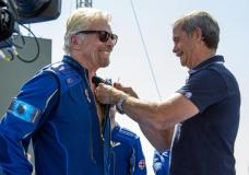 Virgin Galactic founder Richard Branson, left, receives a Virgin Galactic made astronaut wings pin from Canadian astronaut Chris Hadfield after his flight to space from Spaceport America near Truth or Consequences, N.M., Sunday, July 11, 2021. (AP Photo/Andres Leighton)