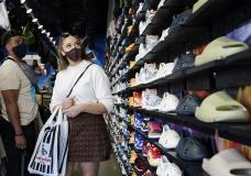 FILE - In this Monday, July 19, 2021, file photo, shoppers wear masks inside of The Cool store in the Fairfax district of Los Angeles. The Centers for Disease Control and Prevention reversed course Tuesday, July 27, 2021, on some masking guidelines, recommending that even vaccinated people return to wearing masks indoors in parts of the U.S. where the coronavirus is surging. (AP Photo/Marcio Jose Sanchez, File)