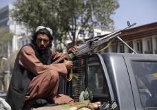A Taliban fighter sits on the back of a vehicle with a machine gun in front of the main gate leading to the Afghan presidential palace, in Kabul, Afghanistan, Monday, Aug. 16, 2021. The U.S. military has taken over Afghanistan's airspace as it struggles to manage a chaotic evacuation after the Taliban rolled into the capital. (AP Photo/Rahmat Gul)