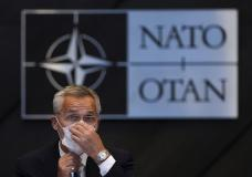 NATO Secretary General Jens Stoltenberg adjusts his protective face mask during a NATO Foreign Ministers video meeting following developments in Afghanistan at the NATO headquarters in Brussels, Friday, Aug. 20, 2021. (AP Photo/Francisco Seco, Pool)