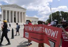FILE - In this Aug. 2, 2021, file photo, voting rights activists march outside of the U.S. Supreme Court, during a voting rights rally on Capitol Hill, in Washington. In the nation's capital on Saturday, Aug. 28, 2021, multiracial coalitions of civil, human and labor rights leaders are convening rallies and marches to urge passage of federal voter protections that have been eroded since the Voting Rights Act of 1965. (AP Photo/Jose Luis Magana, File)