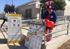 Camille Teran-Grange, a volunteer at polling place at the Montecito Heights Senior Citizen Center in Los Angeles, adds balloons to voter information placards on Tuesday, Sept. 14, 2021. (AP Photo/Stefanie Dazio)