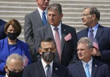 Sen. Joe Manchin, D-W.Va., stands beside Sen. Amy Klobuchar, D-Minn., left, and other lawmakers on the steps of the Capitol during a Sept. 11 remembrance ceremony, in Washington, Monday, Sept. 13, 2021. As congressional Democrats speed ahead this week in pursuit of President Joe Biden's $3.5 trillion plan for social and environmental spending, Manchin, a Democratic senator vital to the bill's fate, says the cost will need to be slashed to $1 trillion to $1.5 trillion to win his support. (AP Photo/J. Scott Applewhite)