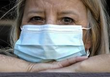 """In this Monday, Sept. 27, 2021, photo Bronwyn Russell poses for a photo at her home in Des Plaines, Ill. Russell, who has had the COVID-19 vaccine, wears a mask anytime she leaves her Illinois home. """"I'm worried. I don't want to get sick,"""" says Russell. (AP Photo/Nam Y. Huh)"""