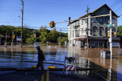 A person walks on a flooded street as the Schuylkill River exceeds its bank in the East Falls section of Philadelphia, Thursday, Sept. 2, 2021 in the aftermath of downpours and high winds from the remnants of Hurricane Ida that hit the area. (AP Photo/Matt Rourke)