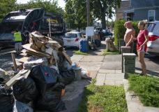 Residents wait a worker picking up debris, Monday, Sept. 6, 2021, in Passaic, NJ., from their flood damaged home in the aftermath of Hurricane Ida. (AP Photo/Eduardo Munoz Alvarez)