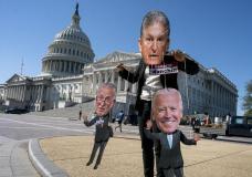 A climate change demonstrator mocks Sen. Joe Manchin, D-W.Va., who has blocked President Joe Biden's domestic agenda, at the Capitol in Washington, Wednesday, Oct. 20, 2021. (AP Photo/J. Scott Applewhite)