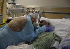 FILE - In this Friday, July 31, 2020, file photo, Romelia Navarro, 64, weeps while hugging her husband, Antonio, in his final moments in a COVID-19 unit at St. Jude Medical Center in Fullerton, Calif. On Monday, Oct. 11, 2021, California's coronavirus death toll reached 70,000. (AP Photo/Jae C. Hong, File)