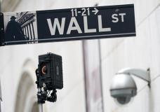 FILE - A Wall Street sign is seen next to surveillance equipment outside the New York Stock Exchange, Tuesday, Oct. 5, 2021, in New York. Stocks fell in morning trading Wednesday, Oct. 6, 2021 as Wall Street undergoes a bout of volatility, driven in part by big swings in technology companies. The S&P 500 fell 0.8%. The benchmark index has risen or fallen by more than 1% the past four days. The Dow Jones Industrial Average slipped 1% and the Nasdaq fell 0.6%. International markets also sold off, with exchanges in Japan, South Korea, Germany and France all dropping more than 1%. (AP Photo/Mary Altaffer)