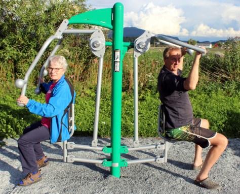 Greta Skjevik og Arne Haug demonstrerer ett av styrkeapparatene på nærmiljøanlegget ved Vinnatrøa