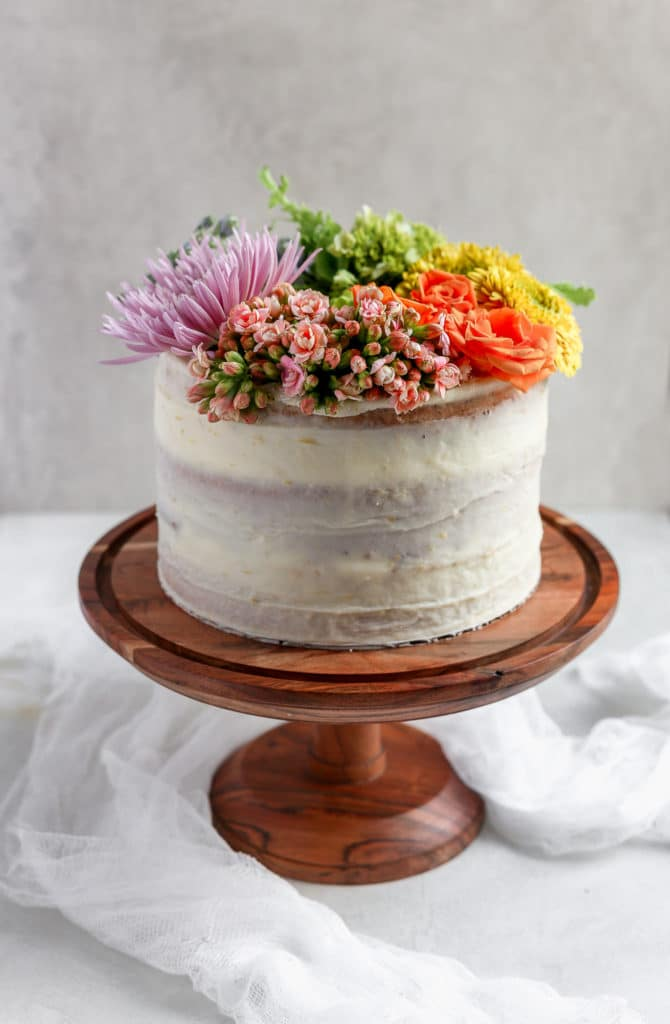 A White Cake On Brown Stand Decorated With Rainbow Of Fresh Flowers Demonstrating