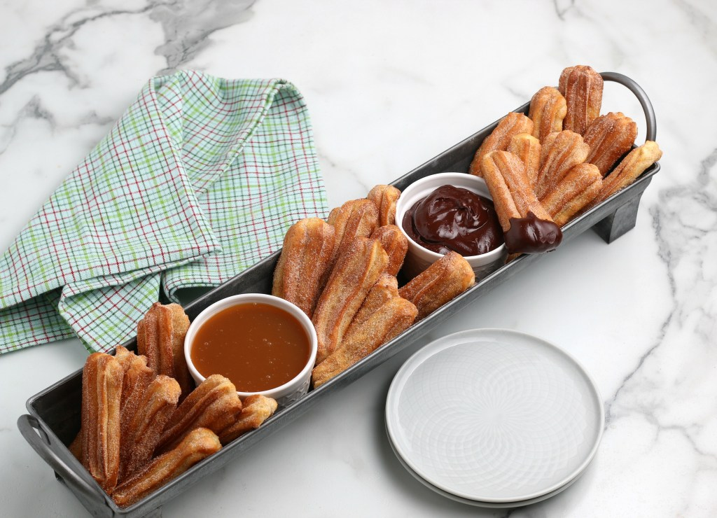 mini air fryer churros and dipping sauces with plates and a tea towel