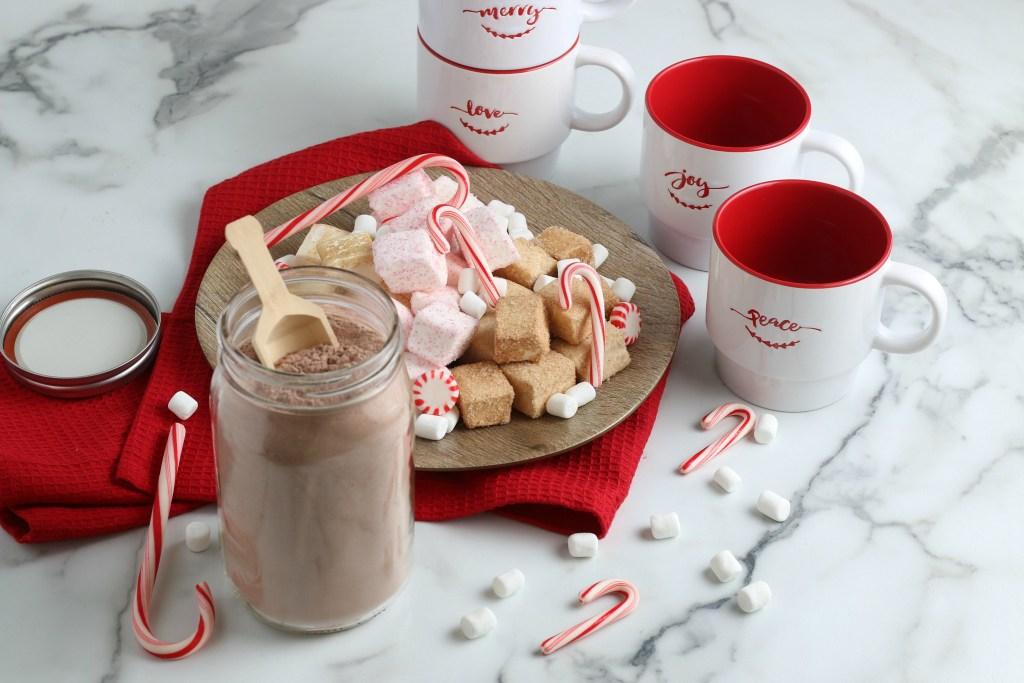 4 Christmas mugs with jar of homemade hot chocolate mix and sweets