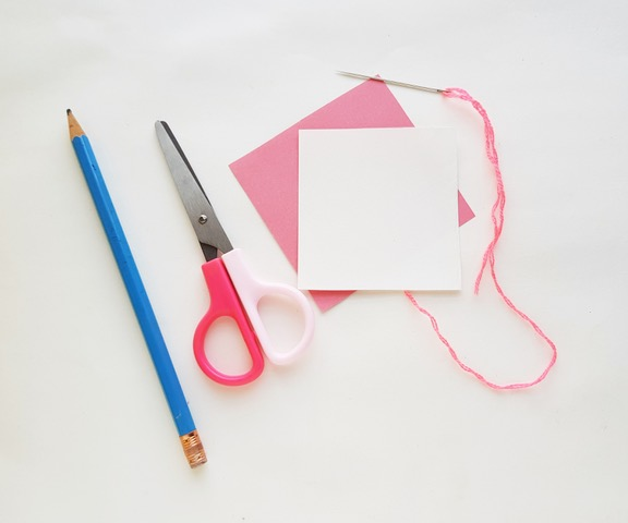 pencil, scissors, yarn, and needled needed for heart stitch craft.