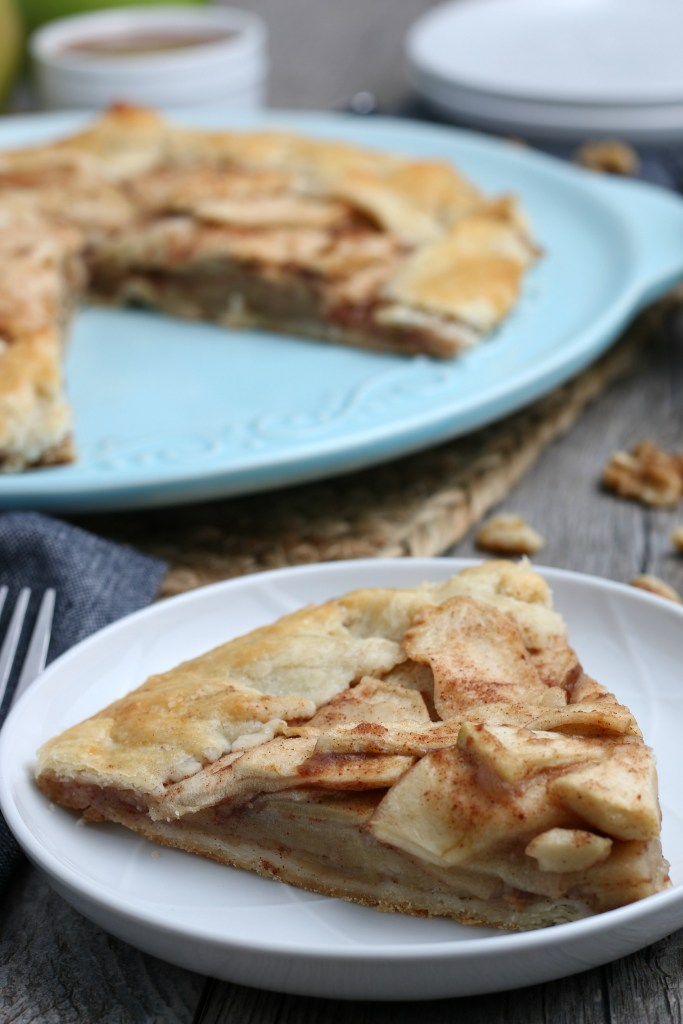 close up of sliced apple crostata with scattered pecans on the counter