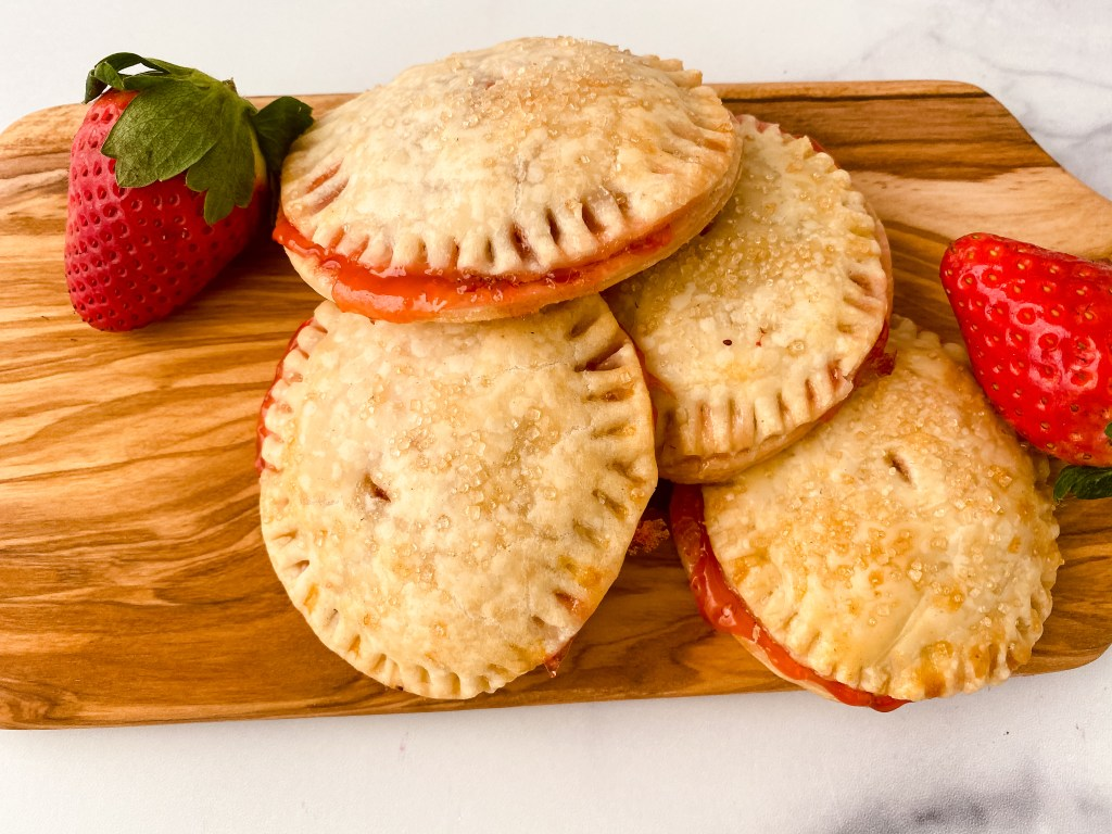 strawberry hand pies and strawberries on a wooden board