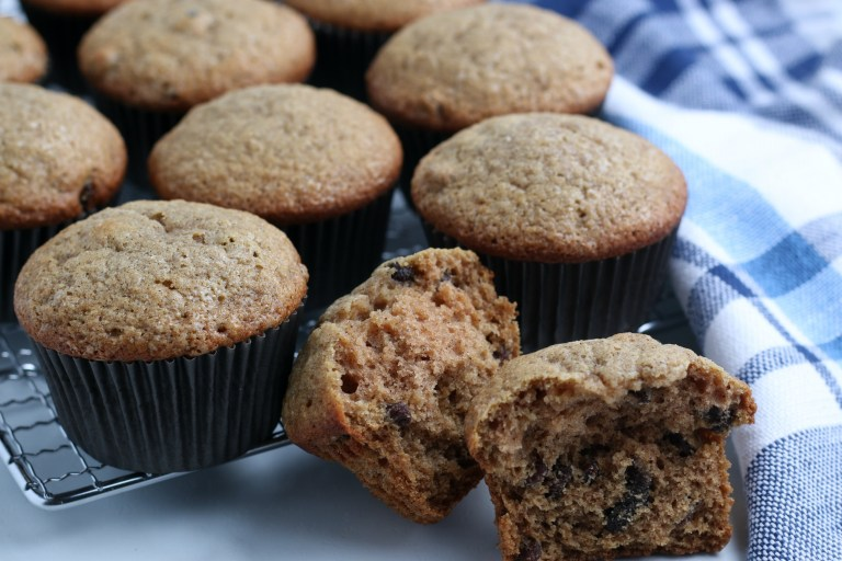 applesauce muffins on a cooling rack with muffin broken in front