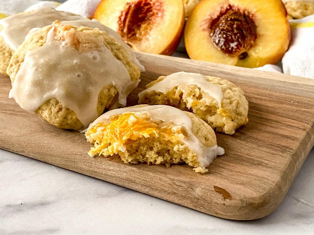 peach cobbler cookies sitting next to peach halves on a wood board