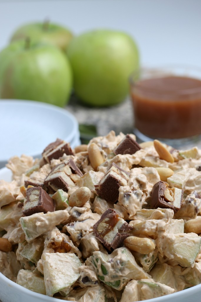 close up of snickers apple salad in a white bowl