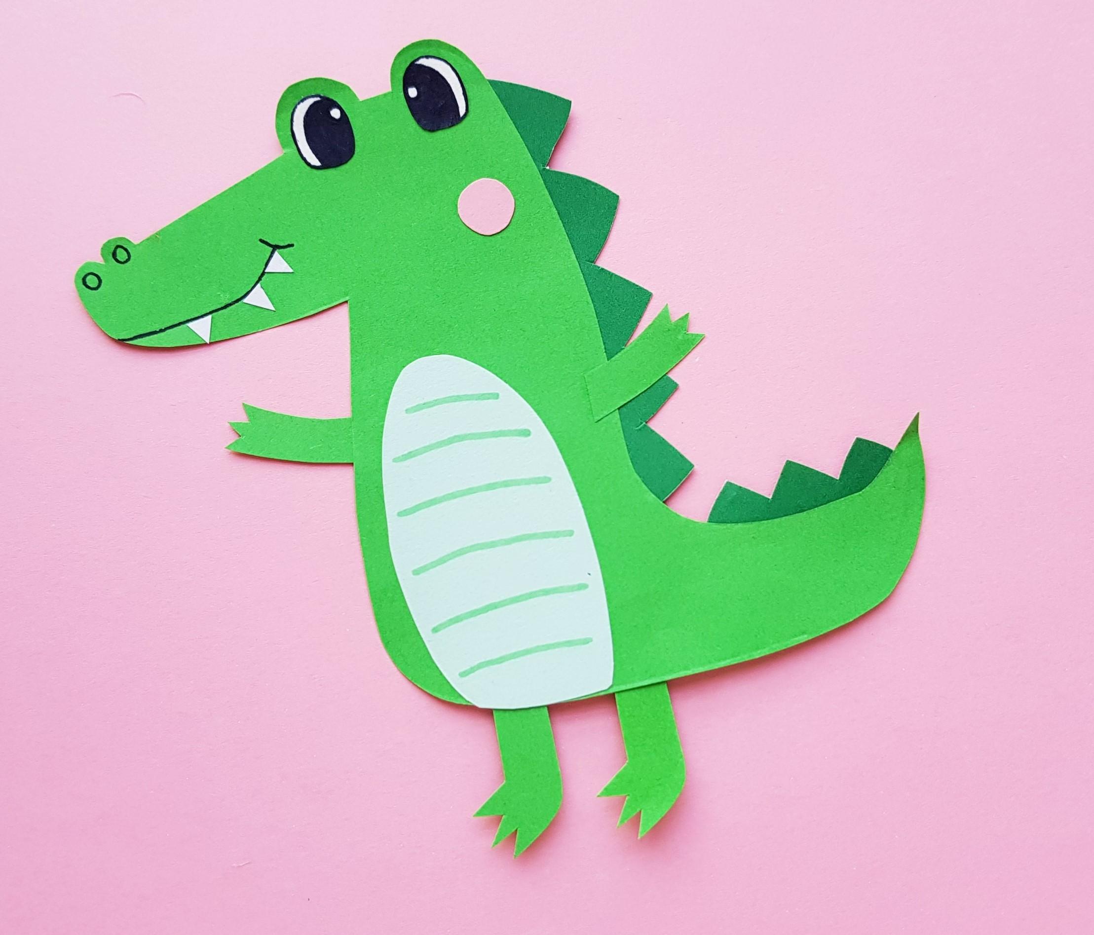 green papercraft alligator on pink paper