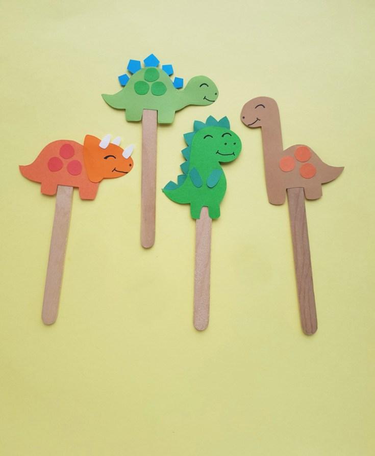 Multiple dinosaur paper craft on popsicle sticks