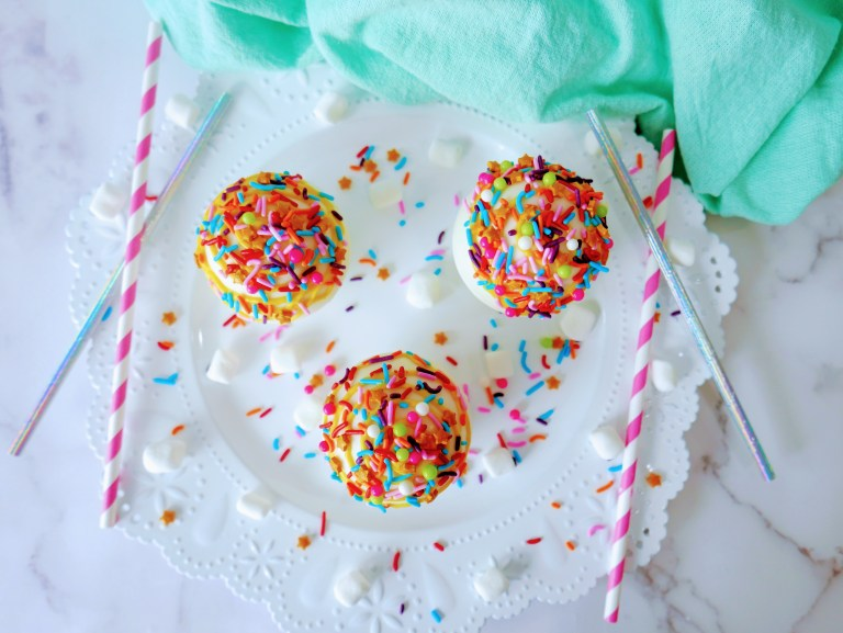 overhead shot of confetti hot chocolate bomb trio with sprinkles and colorful straws