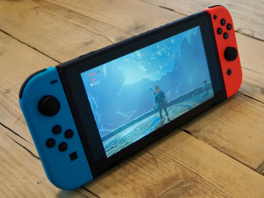 A Nintendo Switch console, showing the game The Legend of Zelda: Breath of the Wild on the screen