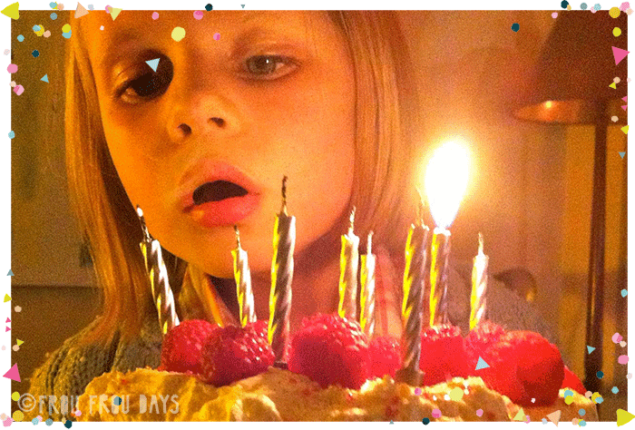 Young girl blowing out birthday candles on cake