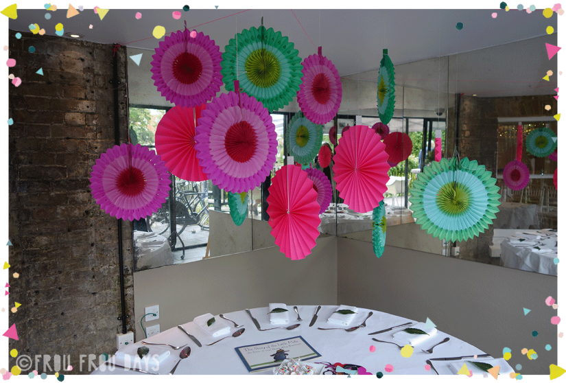 multicoloured party fans hanging over dinner table