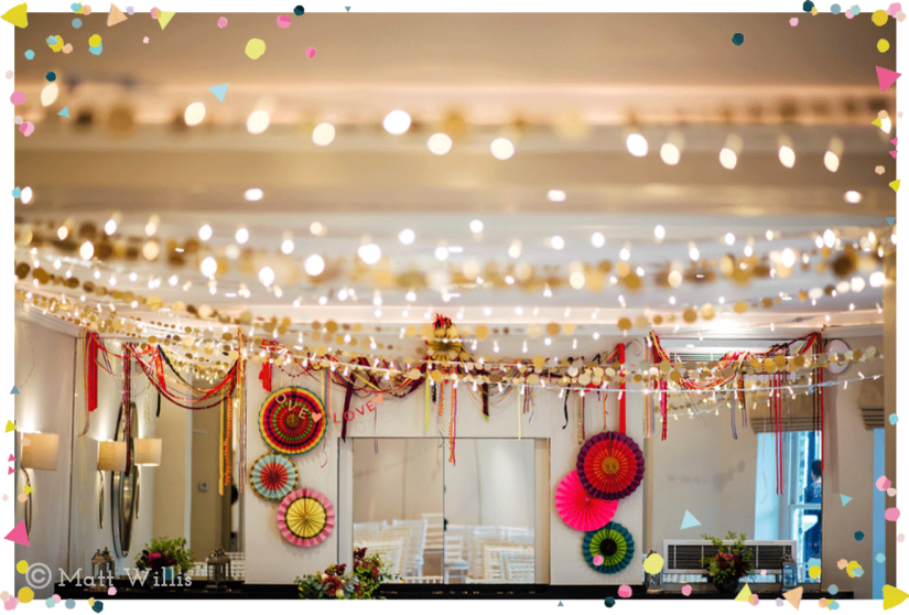 Bollywood English fusion wedding decor fairy lights, gold garlands and bright coloured fans