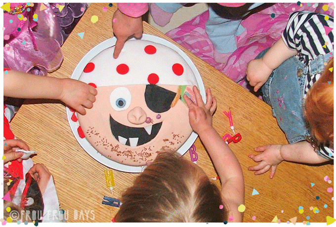 Pirate birthday cake and little children's hands