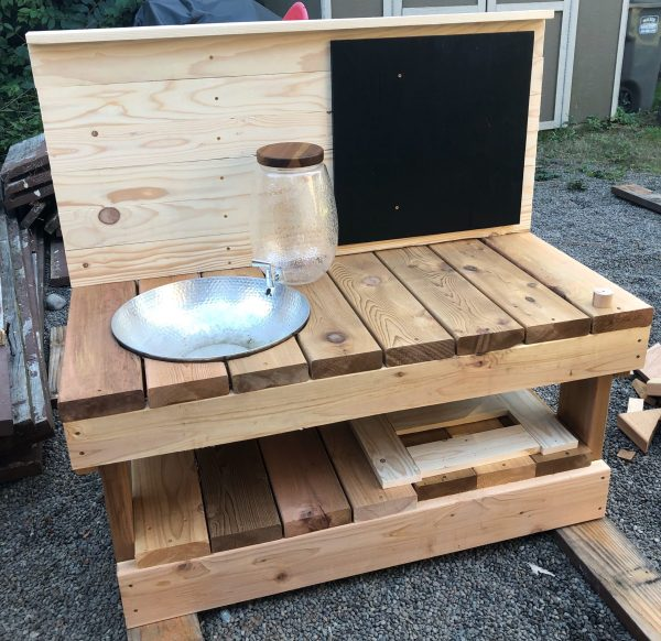 Mud kitchen with water dispenser and sink, chalkboard and top shelf - in progress build in backyard