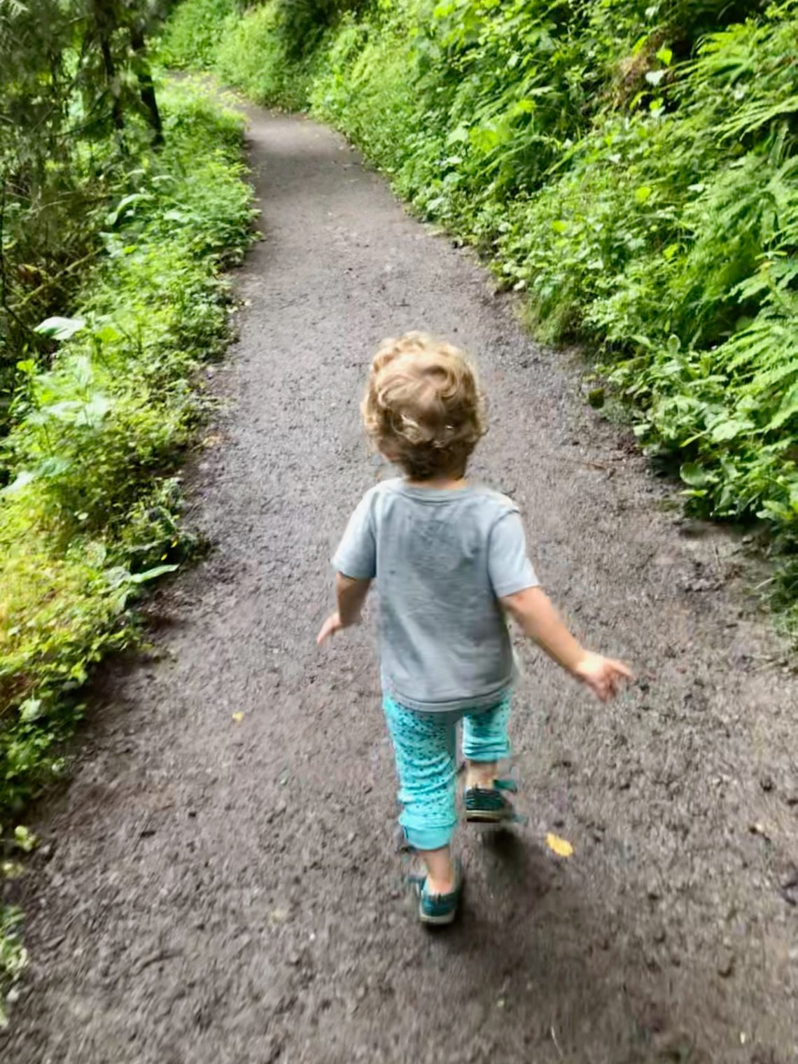 Toddler running down trail in Forest Park