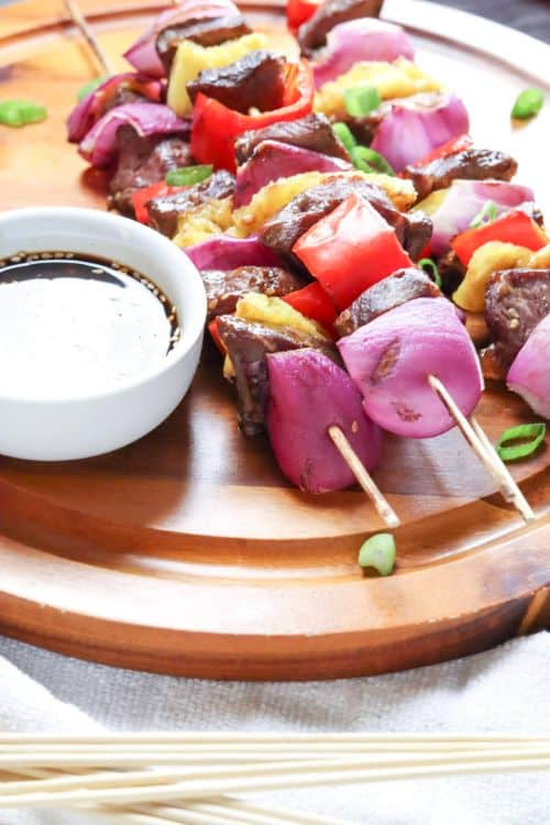 Grilled Steak Kabobs with Homemade Teriyaki Sauce on a wooden plate