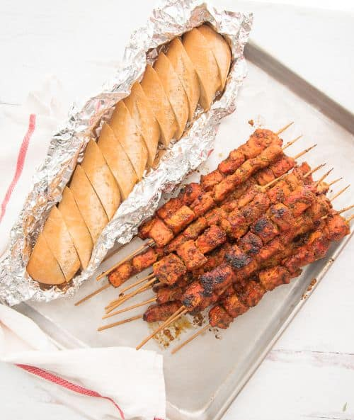 Puerto Rican Grilled Pork Kebabs on a basking sheet with a loaf of bread