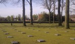 cemetery with grass, trees, and horizontal grave stones