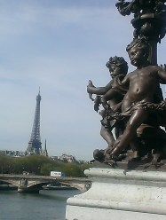 frugal first class travel Eiffel tower in background with cherub statues from Pont Alexandre III in foreground