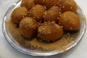 metal plate of Greek donuts with cinnamon and sesame seeds
