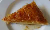 A triangle of Greek dessert on a white plate