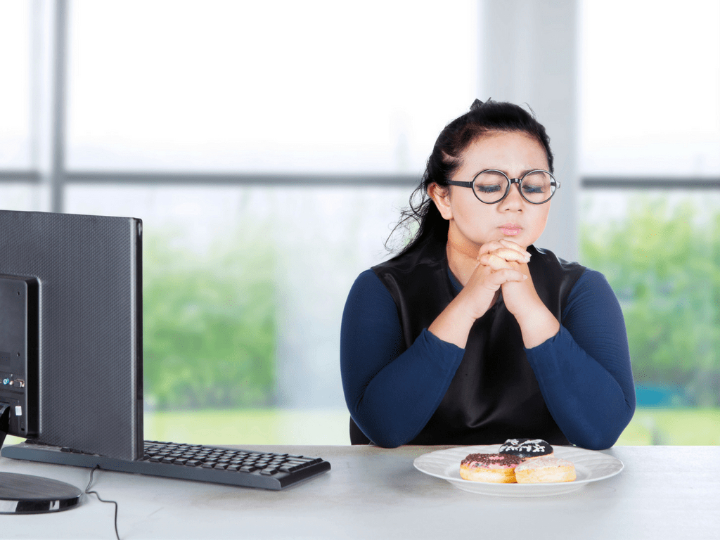 Woman looking at donuts on desk - What Corporate Managers & Stay-At-Home Moms Have In Common