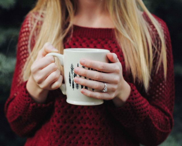 Woman holding cup of coffee - What Corporate Managers & Stay-At-Home Moms Have In Common
