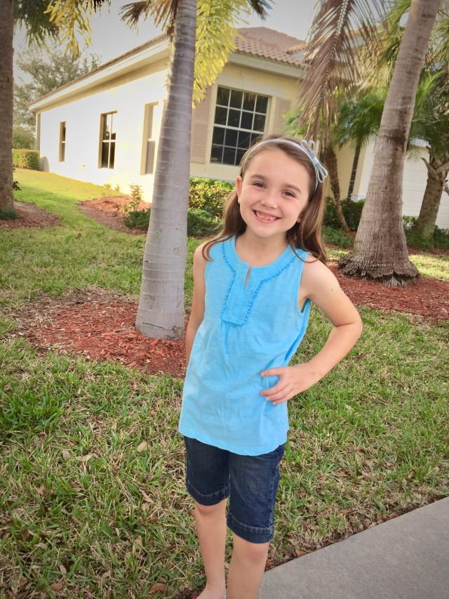 Girl smiling in blue tank top and denim shorts - This Frugal Mom's Favorite Subscription Box